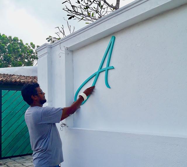 Dinesh setter opp skiltet At Ease Beach Hotel, dagen før hotellet åpner i Hikkaduwa, Sri Lanka